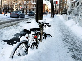 Bikes remain chained to a pole during snow removal hours on rue de Mentana in Montreal on Monday Jan. 2, 2017.