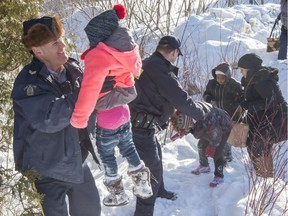 Family members from Somalia are helped into Canada by RCMP officers along the U.S.-Canada border near Hemmingford, Que., on Friday, Feb. 17, 2017.