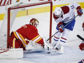 Canadiens' Brendan Gallagher, right, tries to get the puck past Calgary Flames goalie Brian Elliott during second period NHL hockey action in Calgary on Thursday, March 9, 2017.