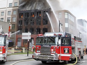 Firefighters battle a fire in a building at the corner of St. Laurent and Viger Sts. in Montreal Thursday November 17, 2016.