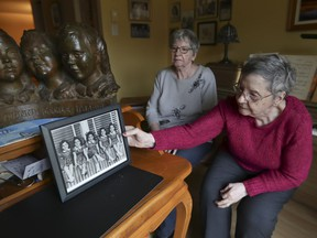 Cécile Dionne (right), with her sister Annette (they are the two surviving Dionne quintuplets, born in Ontario in 1934), with a photo of themselves and their sisters when they were children.
