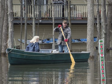 A man and woman use a boat to move along a street in the town of Rigaud, Que., west of Montreal, Thursday, April 20, 2017, following flooding in the area. A state of emergency has been issued for the town.