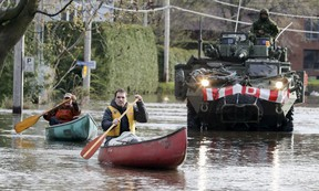 Alain Leroux, right, and Bernard Bégin paddle their canoes to pick up supplies on Blvd. du Lac in Deux Montagnes, northwest of Montreal as Canadian army personnel deliver sandbags Monday, May 8, 2017.