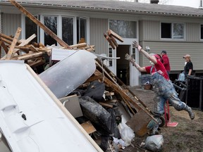Lynn Eaton-Jones carries water soaked wood to a huge pile of debris as she helps a friend gut the basement of a flooded home on Des Maçons Street in Pierrefonds on Saturday, May 13, 2017.