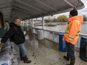 Pointe Claire Yacht Club manager Trevor Collins, wearing orange, and Barry Barnett stand near filled water barrels holding down the clubhouse deck.
