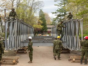 Members of the Canadian Forces install a temporary bridge to Île Verte in Laval on Saturday, May 13, 2017.