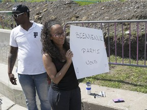 Naomi Jolicoeur and Max LeGrande stand outside Olympic Stadium with sign to welcome Haitian refugees arriving by bus Aug. 2, 2017.
