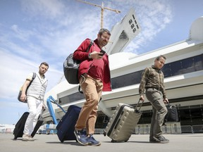 From left, Turkish refugees Cagatay Karaman, Ibrahim Yurtseven and Muhsin Yanik drag their suitcases after leaving the temporary refugee centre at the Olympic Stadium in Montreal on Aug. 7, 2017, after no longer being able to tolerate the living conditions.