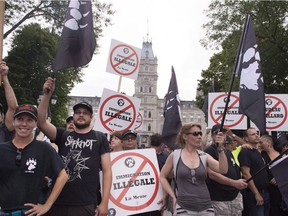 Members of right-wing group La Meute demonstrate in silence in front of the legislature, Sunday, Aug. 20, 2017 in Quebec City.