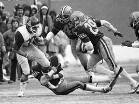 Edmonton Eskimos' Dan Kepley (42) and Joe Hollimon (29) chase Montreal Alouettes' John O'Leary as Eskimos' Herb Dobbins holds on during Grey Cup action in Montreal on Nov. 27, 1977.