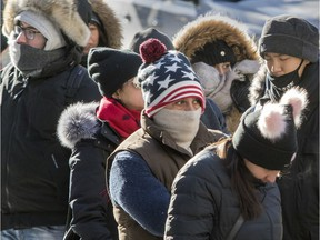 Tourists fight the cold while waiting in line to enter Notre-Dame Basilica in Montreal Sunday, Dec. 31, 2017.