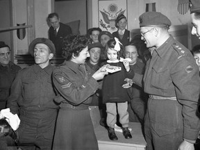 Corporal M. Freeman, Canadian Women's Army Corps (C.W.A.C.), and Captain Samuel Cass, Jewish chaplain, presenting a gift to a Belgian girl during a Hanukkah celebration, Tilburg, Netherlands, Dec. 17, 1944.