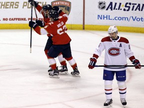 Florida Panthers' Denis Malgin and Vincent Trocheck celebrate after a goal on Saturday, Dec. 30, 2017, in Sunrise, Fla. Canadiens' Tomas Plekanec skates off in dejection.
