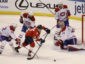 Panthers' Colton Sceviour (7) moves the puck as Canadiens' Byron Froese (42), Jordie Benn (8) Jeff Petry, top right, and goalie Carey Price defend  on Saturday, Dec. 30, 2017, in Sunrise, Fla.