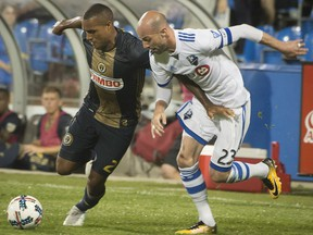 Philadelphia Union's Jay Simpson, left, and Montreal Impact's Laurent Ciman battle for the ball during second half MLS soccer action in Montreal on Wednesday, July 19, 2017.