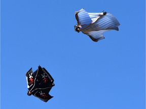 Two men fly in wingsuits.