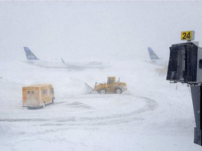Snow plows move snow as a JetBlue airplane waits outside terminal five at John F. Kennedy International Airport on January 4, 2018 in the Queens borough of New York City. A winter storm is traveling up the east coast of the United States dumping snow and creating blizzard like conditions in many areas.