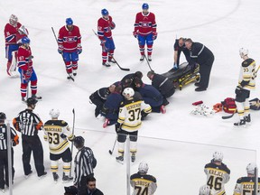Players from the Montreal Canadiens and Boston Bruins look on as Canadiens' Phillip Danault tended to by paramedics after he was hit in the head by a puck on a shot by Bruins' Zdeno Chara (33) during second period NHL hockey action in Montreal, Saturday, January 13, 2018.