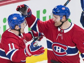 Canadiens' Karl Alzner, right, celebrates with teammate Brendan Gallagher after scoring against the Vancouver Canucks in Montreal on Sunday, Jan. 7, 2018.