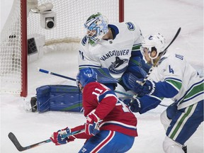 Canucks goaltender Anders Nilsson is scored on by Canadiens' Karl Alzner (not shown) as Canadiens' Brendan Gallagher and Canucks' Michael Del Zotto look on  in Montreal on Sunday, Jan. 7, 2018.