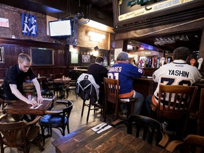 Adam Ramsey prepares tables as a few hockey fans sit at the bar in McLean's Pub on Wednesday, Feb. 28, 2018.
