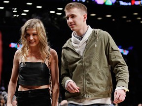 Genie Bouchard, walks the court with her blind date, John Goehrke, right, during the first half of an NBA basketball game between the Brooklyn Nets and the Milwaukee Bucks Wednesday, Feb. 15, 2017, in New York. They will be attending Super Bowl LII together.