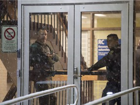 Police stand in the front doors of the courthouse in Maniwaki, Que. after a shooting there last week.