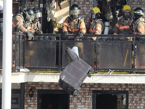 Firefighters clear debris after a fire at the Econo Lodge Motel in Brossard in March.