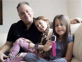 Adam Dorfman, seen at his Dollard home with his daughters Caleigh and Sierra, sells GPS tracking bracelets for children.