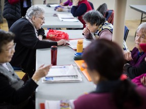 Violet Campbell, back left, helps Wu Xiao Yun, back right, during a weekly group meeting to help people practice their English skills, combat social isolation and foster relationships, in Vancouver, B.C., on Friday February 23, 2018. The problem of social isolation, which can have serious consequences on a person's mental health and mortality, gained international awareness when the United Kingdom appointed a minister of loneliness in January.