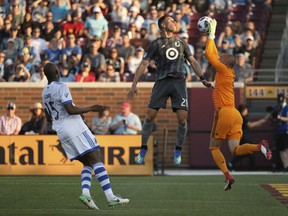 Minnesota United forward Christian Ramirez (21) goes up for a head ball as Montreal Impact goalkeeper Evan Bush (1) makes a leaping save during the first half on May 26, 2018, in Minneapolis.