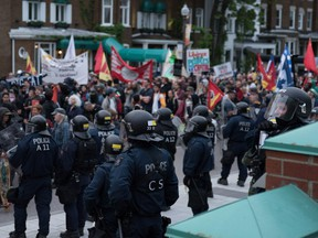 Protestors march before riot police during an anti-G7 demonstration in Quebec City, Quebec, June 7, 2018, on the eve of the leaders' summit.