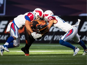 Alouettes' Branden Dozier (1) and Mitchell White tackle Lions' Jeremiah Johnson during first half last week in B.C.