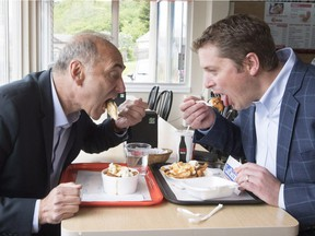 Conservative Leader Andrew Scheer, right, and Saguenay-Le Fjord candidate Richard Martel take a eat poutine at the famous Boivin cheese counter, Thursday, June 14, 2018 in Saguenay Que.