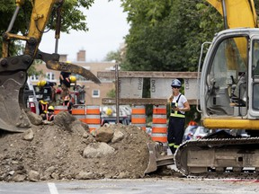 An Énergir stands by after a work crew installing a new sewer to a residential building under renovation punctured a natural gas line on Girouard Ave. just north of Monkland Ave. in July 2018.