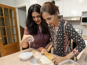 Meena Khan and her mother, Nikhat Khan, make chapatis in their home. Living at home allows her to help look after her aging parents, Meena Khan says.