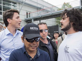 Prime Minister Justin Trudeau, left, is confronted by Matthieu Brien, 31, during a visit to a Quebec's Fete nationale holiday celebration in Montreal, Saturday, June 23, 2018.