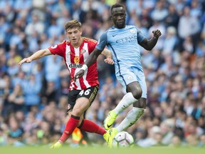 Manchester City's Bacary Sagna, right, fights for the ball against Sunderland's Lynden Gooch during English Premier League soccer match between Manchester City and Sunderland at the Etihad Stadium in Manchester, England, on Aug. 13, 2016.