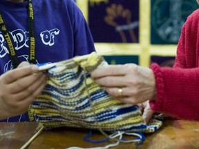 A volunteer teaches knitting techniques to a high school student: In several schools, elders run the breakfast club, helpwith reading circles and extra-curricular activities such as the knitting andchess clubs, Don Rosenbaum writes.