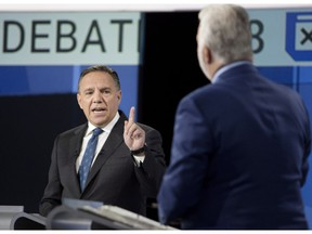 CAQ Leader François Legault, left, speaks to Liberal Leader Philippe Couillard, during their English language debate, Monday, September 17, 2018 in Montreal, Que. In Thursday's French-language debate, there was a revealing exchange between the two men on the wearing of signs of religion by those wielding state authority.