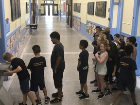 Students at Roslyn Elementary School in Westmount line up for the water fountain as students across Montreal try to beat the heat.