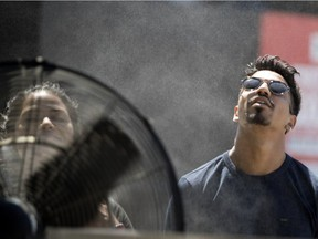 MONTREAL, QUE.: JULY 3, 2018-- Xavier Selly cools down in front of a large fan that is equipped with a water misting ring at the Montreal International Jazz Festival as Montreal endures a heat wave on Tuesday July 3, 2018. (Allen McInnis / MONTREAL GAZETTE) ORG XMIT: 60989