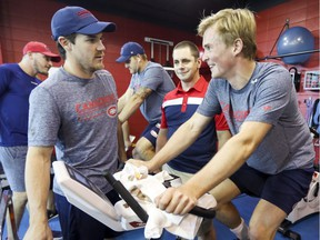 Montreal Canadiens' Andrew Shaw, front left, talks with Artturi Lehkonen as he rides a stationary cycle on the first day of training camp at the Bell Sports Complex in Brossard on Sept. 13, 2018. Athletic therapist Jean-Luc Gohier supervises Lehkonen's performance.