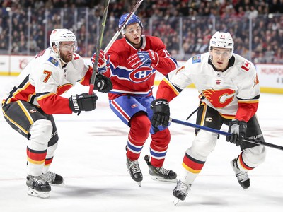 Jesperi Kotkaniemi tries to get to the net between TJ Brodie, left, and Mikael Backlund of the Calgary Flames during first period in Montreal Tuesday, Oct. 23, 2018.