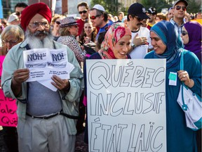 "People take part in a protest against the proposed Charter of Quebec Values in Montreal on Sunday, September 29, 2013. Hearing Coalition Avenir Québec's plans, ""I felt like someone hit reset and it was 2013, and the Charter of Values had just been announced,"" Fariha Naqvi-Mohamed writes."
