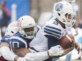 Toronto Argonauts quarterback James Franklin is tackled by Montreal Alouettes' Henoc Muamba during first half CFL football action in Montreal, Sunday, Oct. 28, 2018.