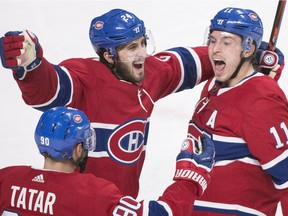 Canadiens' Tomas Tatar, Phillip Danault, centre, and Brendan Gallagher celebrate Gallagher's late goal Wednesday night against the Blues at the Bell Centre.