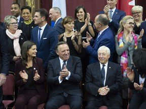 Quebec Premier François Legault, centre, celebrates with his new cabinet and Quebec Lt.-Gov. J. Michel Doyon, right, after he and his cabinet were sworn in during a ceremony at the National Assembly on Thursday.