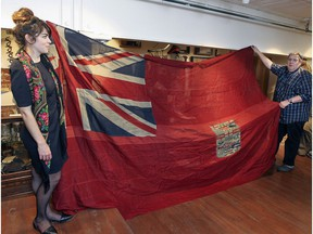 Curator Caitlin Bailey and collector Mark Cahill unfold a red ensign, the Canadian flag during World War 1, at Cahill's Canadian Centre for the Great War, in 2015.