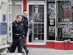 Police investigators leave Cafe Cubano, the scene of an overnight shooting in Montreal Nov. 7, 2018.